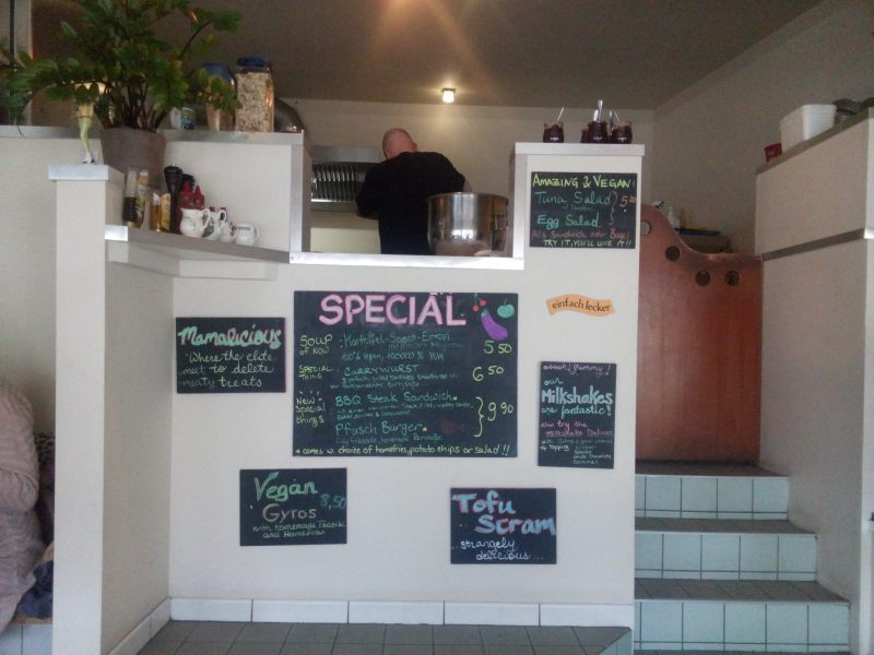 cardapio em frente a cozinha aberta, contando com burgers, currywurst, gyros e outras delicias